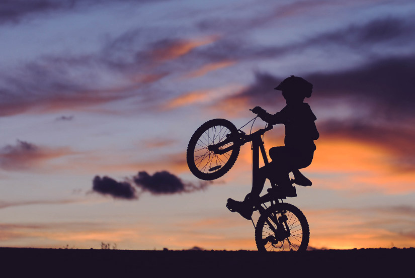 Silhouette of kid on mountain bike doing wheelie